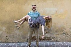Couples heureux dans l'amour sur la rue devant un mur en pierre Photo libre de droits