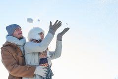 Couples heureux dans la boule de neige de lancement d'hiver Images stock