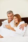 Couples heureux dans la chambre d'hôtel avec la tablette Images stock