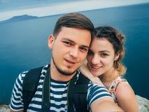 Couples heureux dans la fille d'amour et son ami faisant un selfie en voyage aux vacances à la mer Photos stock