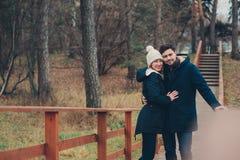 Couples heureux dans la marche tricotée chaude de chapeau et d'écharpe extérieure dans la forêt d'automne Images libres de droits