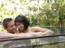 Couples heureux dans la piscine photographie stock libre de droits