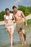 Couples heureux dans la promenade de vêtements de bain dans le lac Photo libre de droits