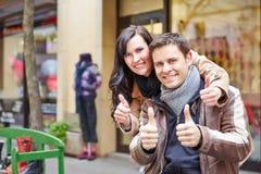 Couples heureux dans la ville tenant des pouces Photos stock