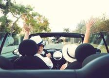 Couples heureux dans la voiture avec les bras augmentés Photographie stock