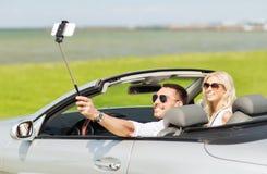 Couples heureux dans la voiture prenant le selfie avec le smartphone Photos stock