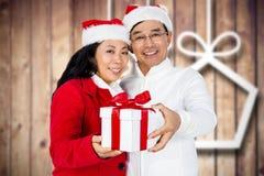 Couples heureux dans le chapeau de Santa tenant le cadeau de Noël Image stock