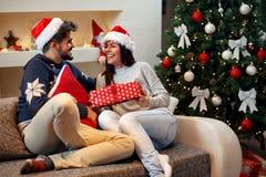 Couples heureux dans le chapeau du ` s de Santa avec des cadeaux de Noël Image libre de droits