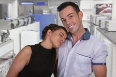 Couples heureux dans le magasin d'électro-ménagers Images libres de droits