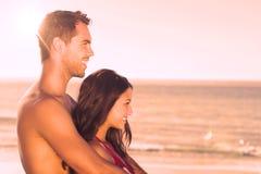 Couples heureux dans le maillot de bain étreignant tout en regardant l'eau Images stock