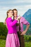 Couples heureux dans le pré alpin dans Tracht Image stock