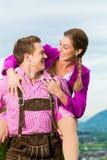 Couples heureux dans le pré alpin dans Tracht Images stock