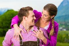 Couples heureux dans le pré alpin dans Tracht Photo libre de droits