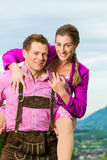 Couples heureux dans le pré alpin dans Tracht Images libres de droits