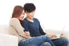 Couples heureux dans le sofa avec l'ordinateur portable à la maison Images libres de droits