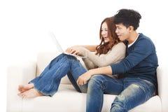 Couples heureux dans le sofa avec l'ordinateur portable à la maison Photographie stock