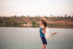 Couples heureux dans les étreintes de coucher du soleil dans l'eau Un homme élève une femme dans des ses bras et la tourne autour photographie stock libre de droits