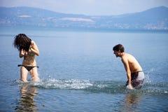 Couples heureux dans les vacances éclaboussant l'eau à l'un l'autre Image libre de droits