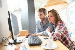 Couples heureux dans un cybercafe websurfing Photographie stock libre de droits