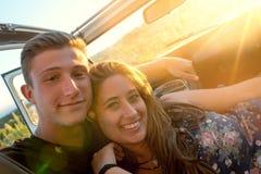 Couples heureux dans une voiture Images stock