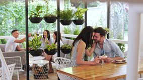 Couples heureux de  de Ð mangeant un dessert au café Couples affectueux étreignant au café clips vidéos