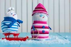 Couples heureux de bonhomme de neige en hiver se reposant avec un traîneau Photographie stock libre de droits