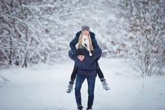Couples heureux de course de l'hiver Homme donnant le tour de ferroutage de femme des vacances d'hiver dans la forêt neigeuse Images stock