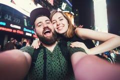 Couples heureux de datation dans l'amour prenant la photo de selfie sur le Times Square à New York tandis que voyage aux Etats-Un Images stock