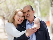 Couples heureux de famille étreignant en parc Images libres de droits