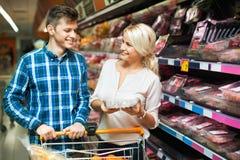 Couples heureux de famille choisissant la viande réfrigérée photographie stock