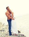 Couples heureux de famille dans l'amour étreignant et riant sur la plage Photo libre de droits
