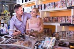 Couples heureux de famille sélectionnant la vidéo et le sourire érotiques photos stock