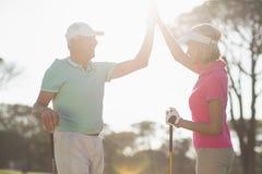 Couples heureux de golfeur donnant la haute cinq Photo libre de droits