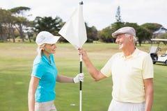 Couples heureux de golfeur tenant le drapeau blanc Image libre de droits