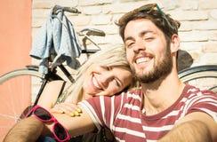 Couples heureux de hippie prenant le selfie au vieux voyage de ville avec la bicyclette Photo stock