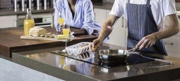 Couples heureux de jeune métis préparant le petit déjeuner dans la cuisson de cuisine Photo libre de droits