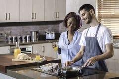 Couples heureux de jeune métis préparant le petit déjeuner dans la cuisson de cuisine Photos stock