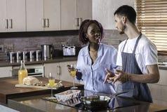 Couples heureux de jeune métis préparant le petit déjeuner dans la cuisson de cuisine Images stock