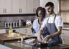 Couples heureux de jeune métis préparant le petit déjeuner dans la cuisson de cuisine Photographie stock libre de droits
