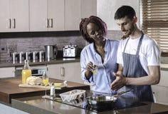 Couples heureux de jeune métis préparant le petit déjeuner dans la cuisson de cuisine Photo stock