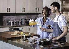 Couples heureux de jeune métis préparant le petit déjeuner dans la cuisson de cuisine Image stock