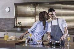 Couples heureux de jeune métis préparant le petit déjeuner dans la cuisson de cuisine Image libre de droits