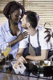 Couples heureux de jeune métis préparant le petit déjeuner dans la cuisson de cuisine Photographie stock