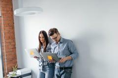 Couples heureux de mélange-course tenant l'ordinateur portable tout en se tenant et célébrant d'isolement au-dessus du fond gris  Photographie stock