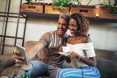 Couples heureux de métis ayant l'amusement au café Photos stock