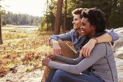 Couples heureux de métis détendant dans la campagne Image stock