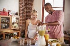 Couples heureux de métis faisant des smoothies, utilisant le mélangeur Photo libre de droits