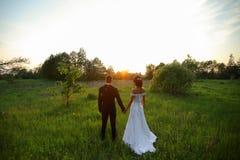 Couples heureux de mariage au coucher du soleil Image stock