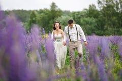 Couples heureux de mariage dans le lupin Images stock