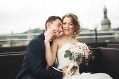 Couples heureux de mariage, jeune mariée, marié embrassant avec la vue de la vieille ville Image libre de droits